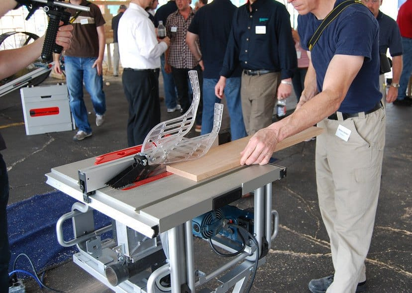 A man uses a portable and mobile table saw on site