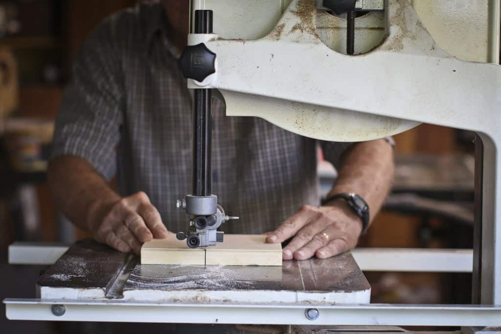 A man uses a bandsaw to cut a piece of wood
