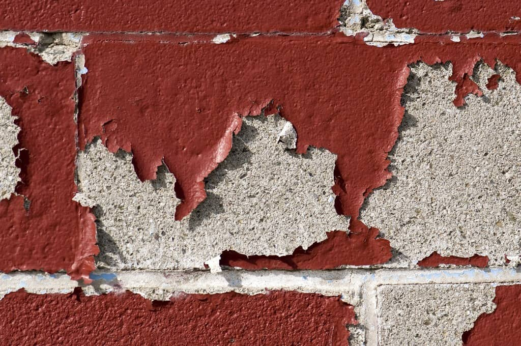 paint chipping on a faux brick wall
