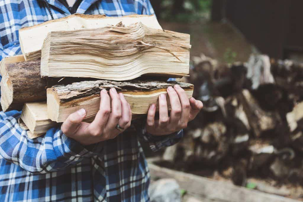 man carrying a stack of wood from a log
