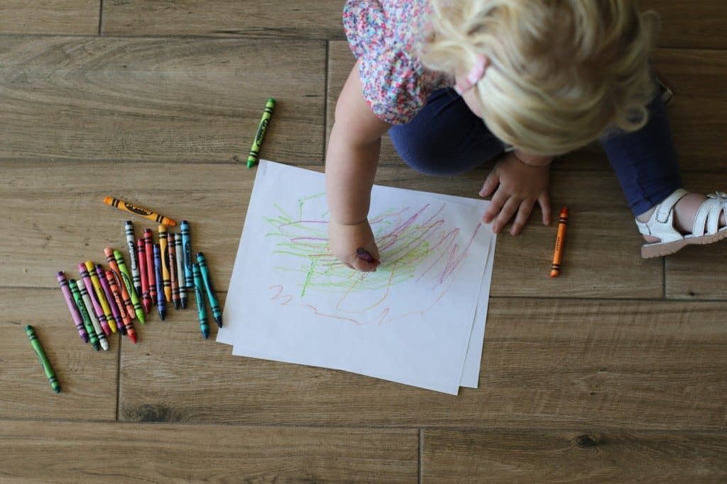 kid coloring with crayons on wood floor