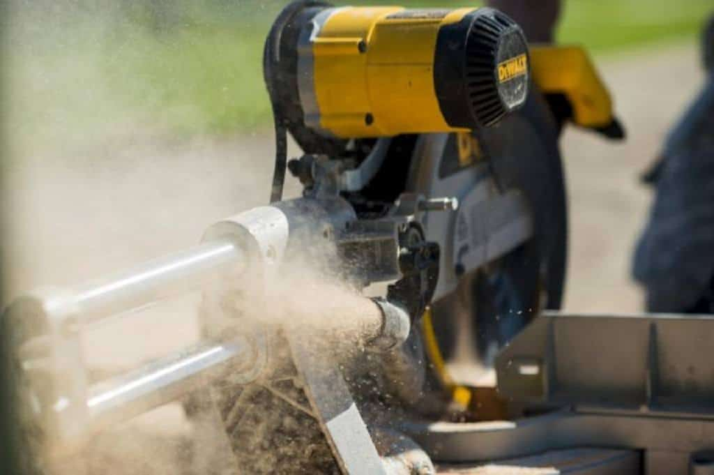 Dust shooting out from a pipe out of a miter saw