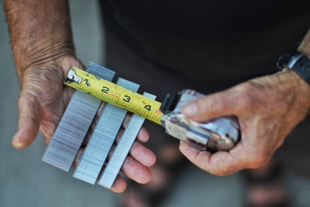 Man holds a tape measure to show sizes of various brad nail lengths