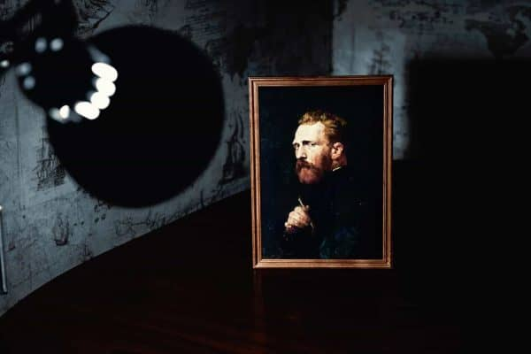 Lamp putting a spot light on a painting of man on a table