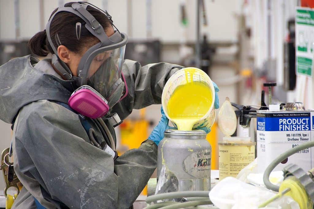 Woman puts yellow paint in a paint sprayer
