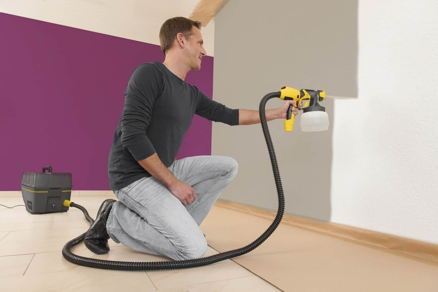 Man in a casual outfit uses a HVLP paint sprayer to paint the walls of his home gray and purple