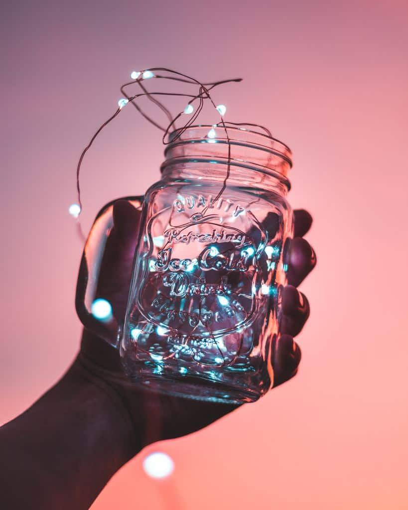 A hand holding a jar with fairy lights inside