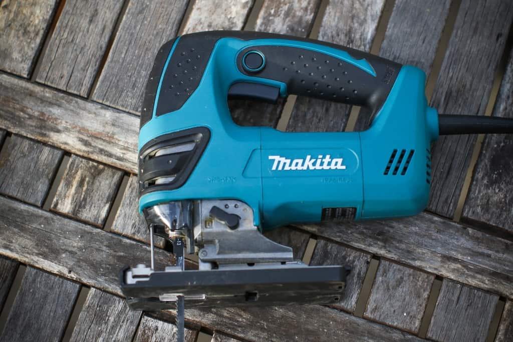 Blue Makita jigsaw on wood