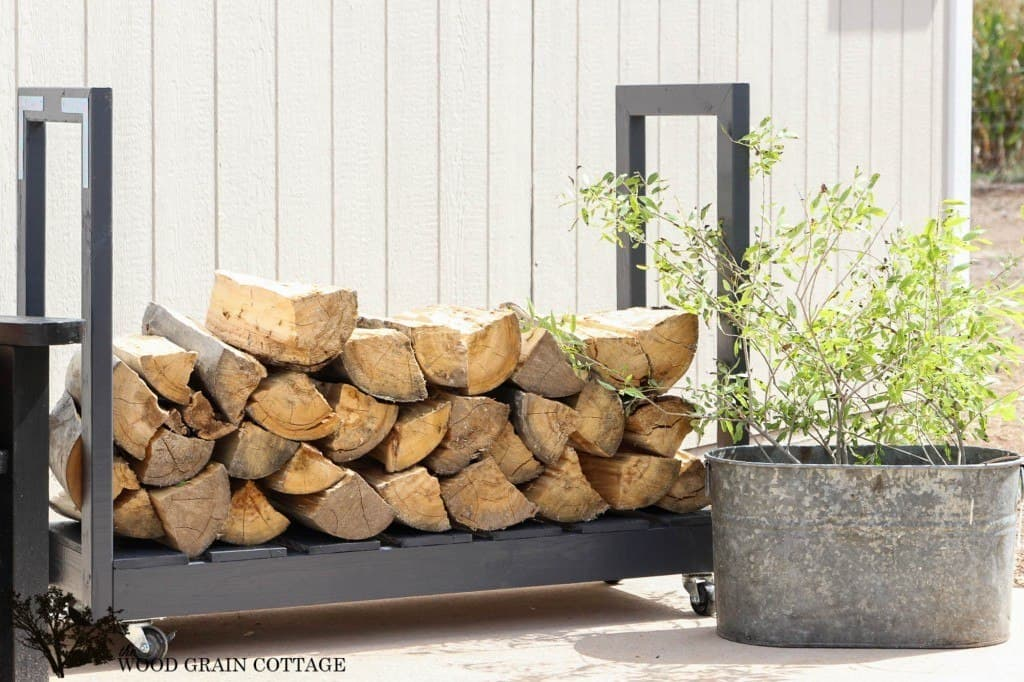 A dark gray firewood storage bench