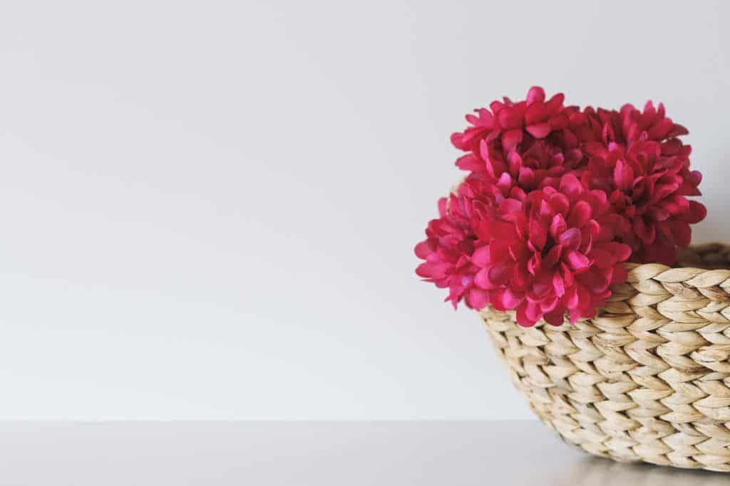A woven basket with pink flowers