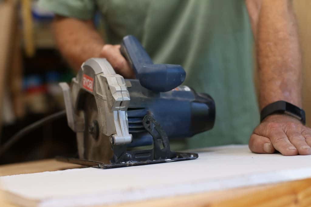 A man uses a circular saw for cutting cement backer