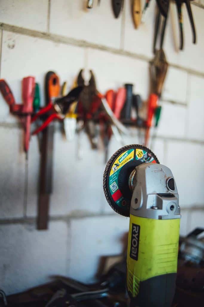 A green Ryobi angle grinder in a garage