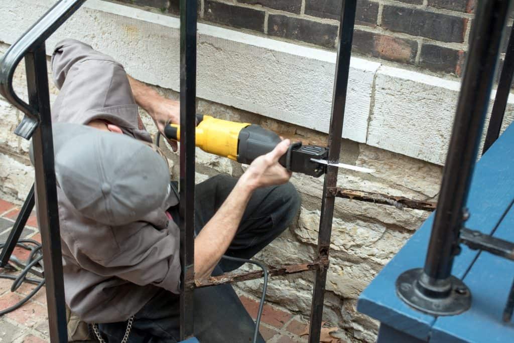 Man using a reciprocating saw to cut through metal