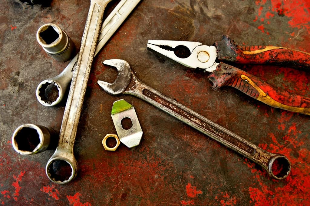Bunch of tools, nuts and sockets on the rusty table