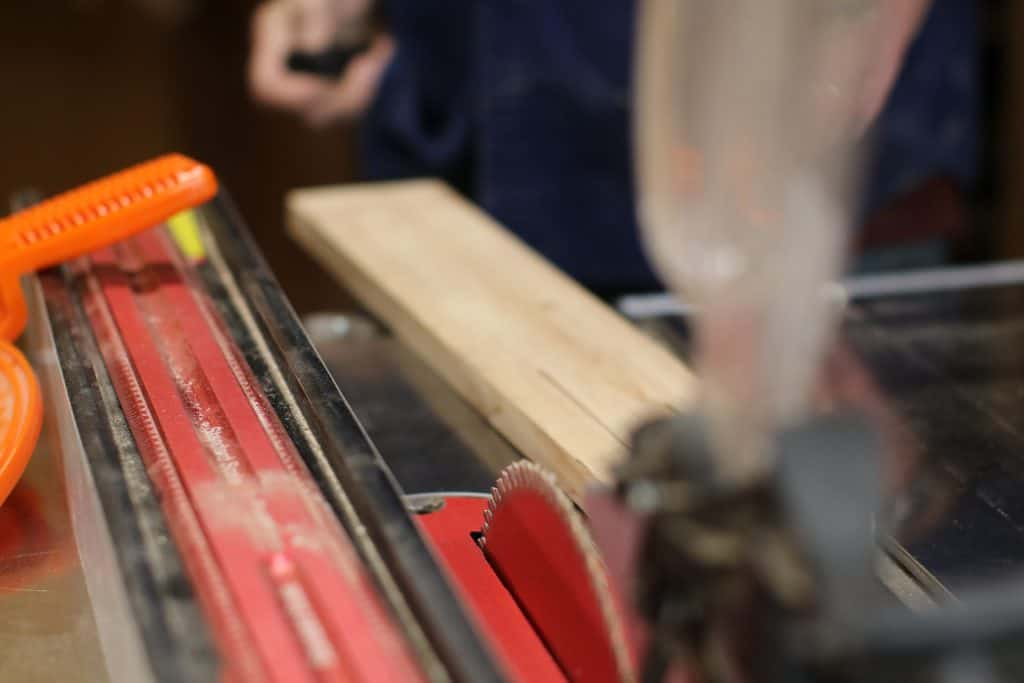 A table saw fence sits by the blade ready to guide the wood for a rip cut