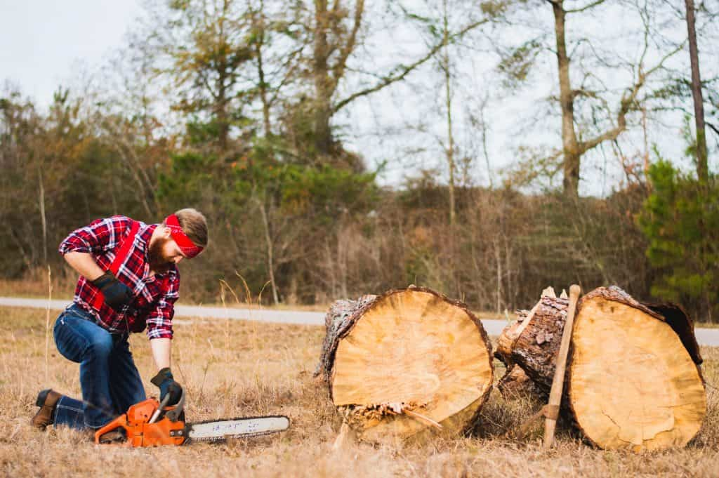 A man uses a budget chainsaw to cut lumber