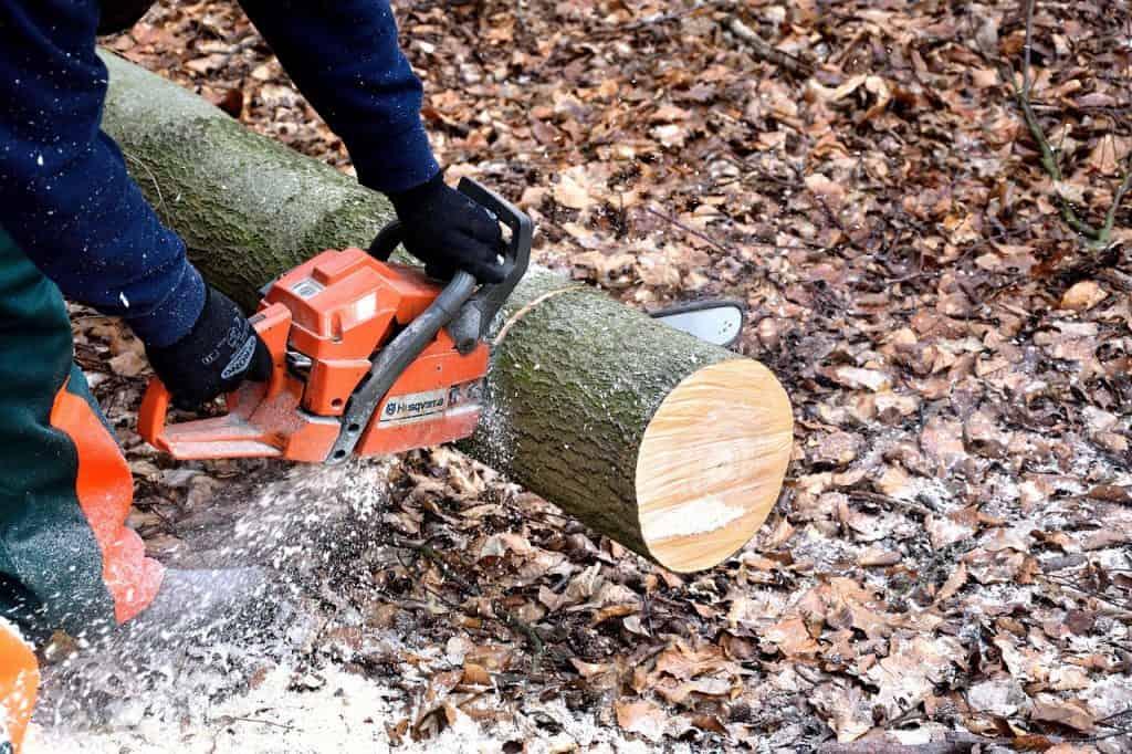 A man uses a Husqvarna chainsaw to cut through a log