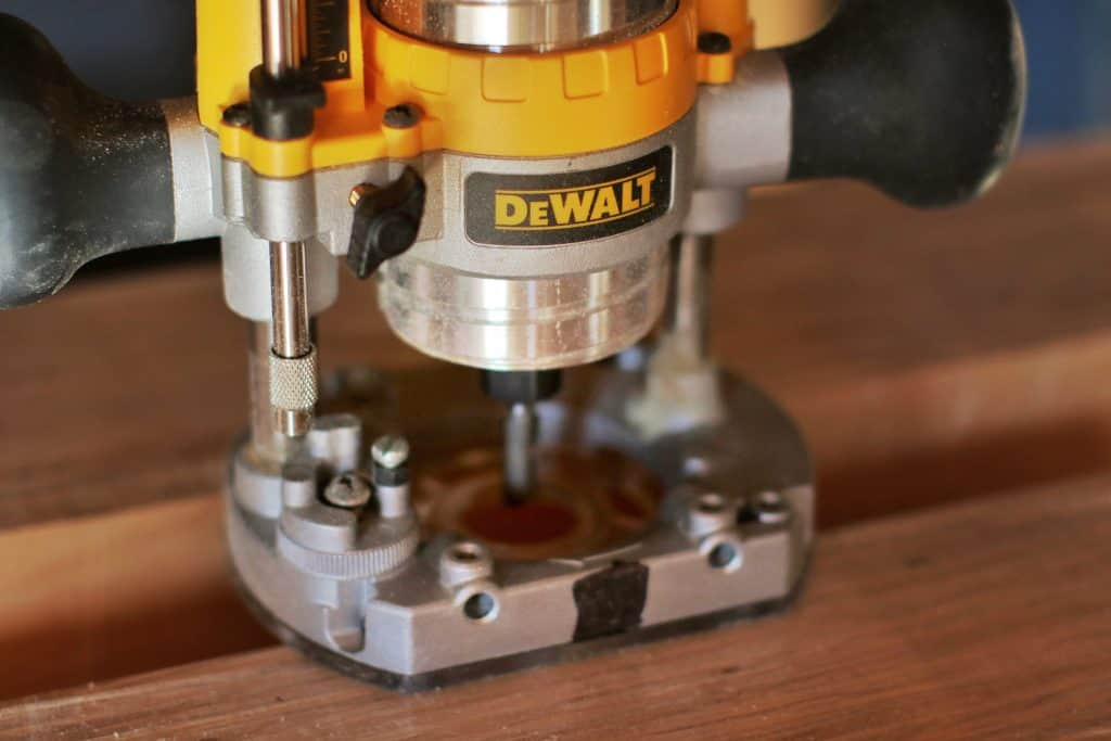 A Dewalt brand plunge style router sits on a piece of wood