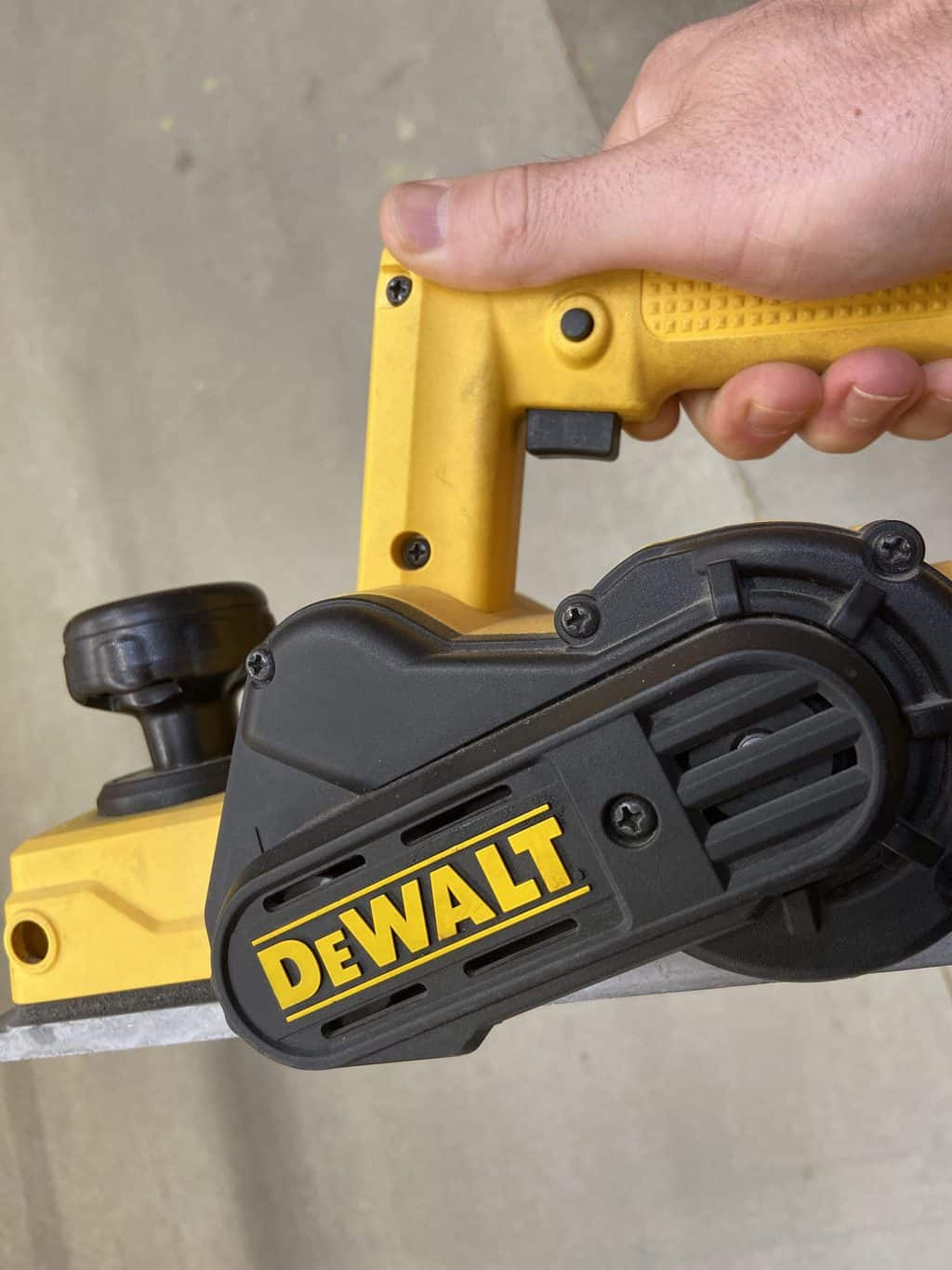 A man holds and electric powered hand planer