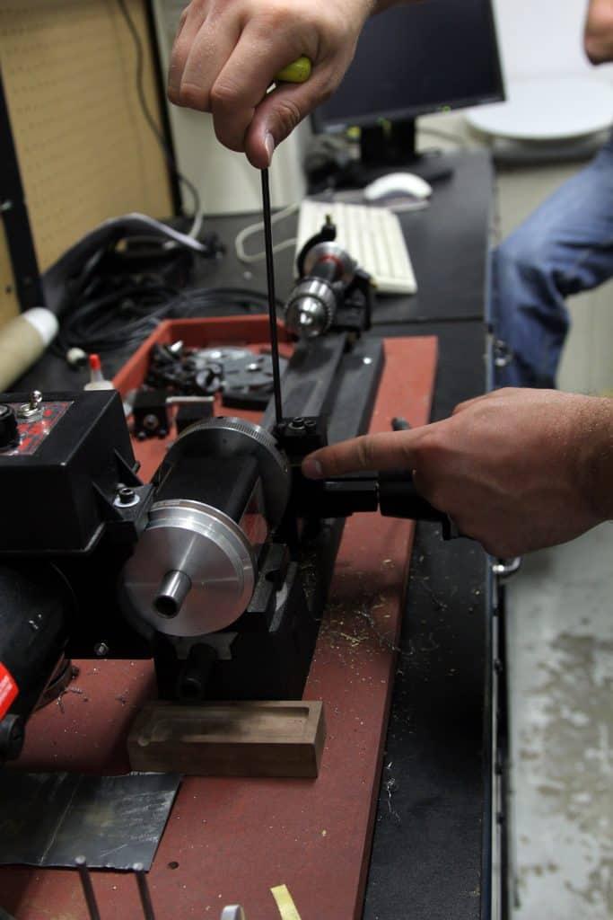 A person preparing a mini lathe for use