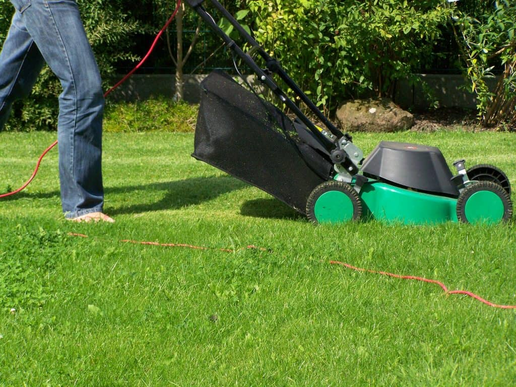 A person clearing the grass using a lawn mower