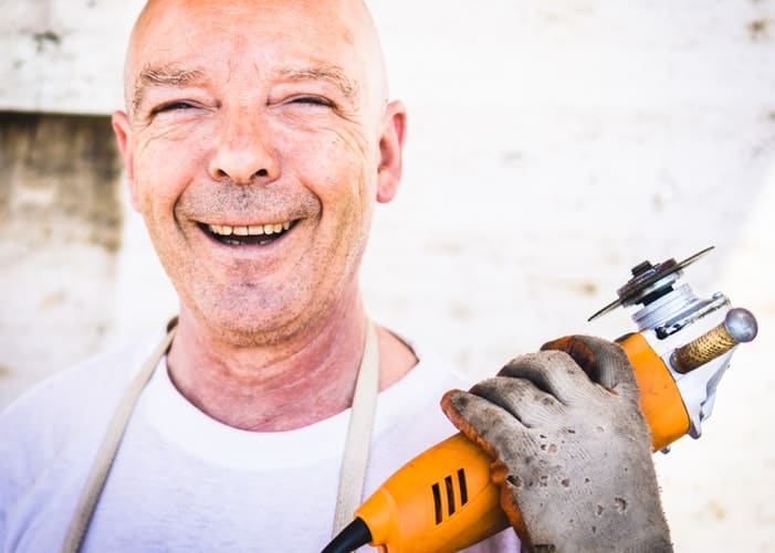 Man smiling and holding an angle grinder instead of a cut off tool