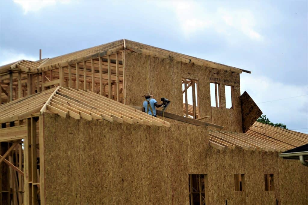 Man holding a framing nailer while on top of a roof of a house under construction