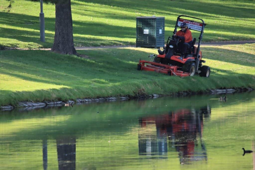 Man using a lawn mower on an uneven grass terrain