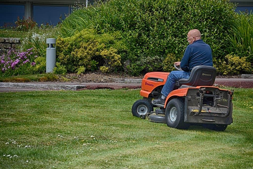 Man riding a lawn mower to trim the grass hills