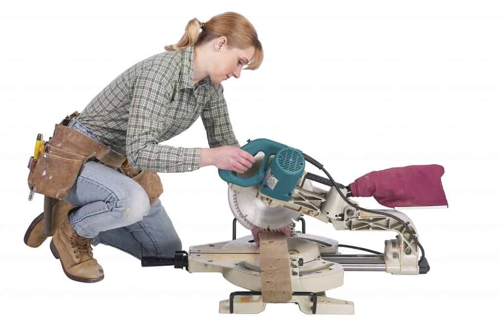 Woman crouching down on her knees while using a circular saw to cut a narrow piece of wood