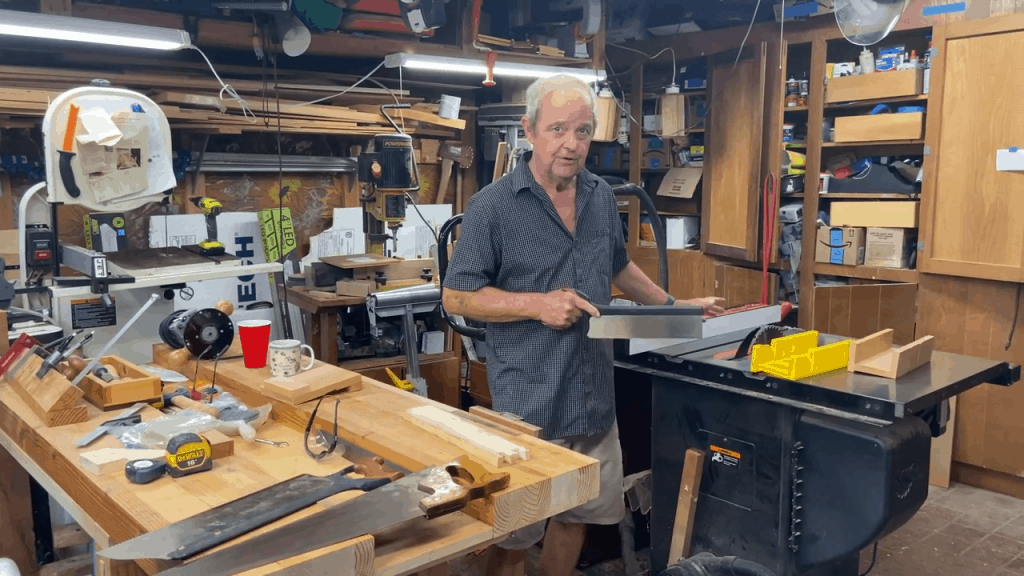 Man holding a metal cutter beside a table saw