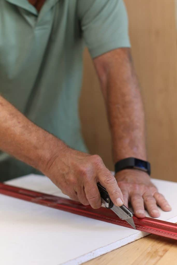 Man uses the score and snap method to cut cement board