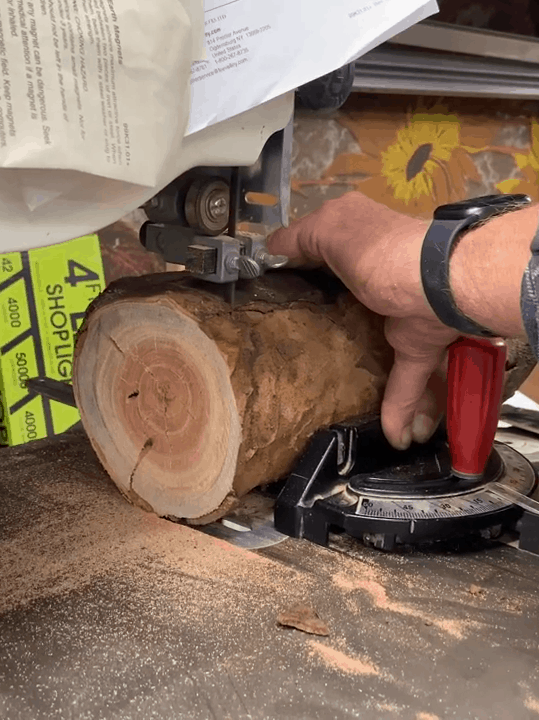 Man using a bandsaw to cut wood in slices