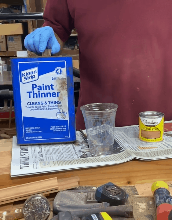 Man pointing to a paint thinner canister beside a can of wood stain