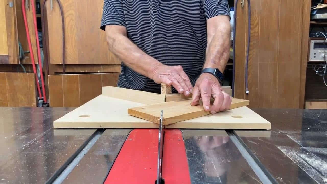 Man showing how to cut a triangle on a table saw