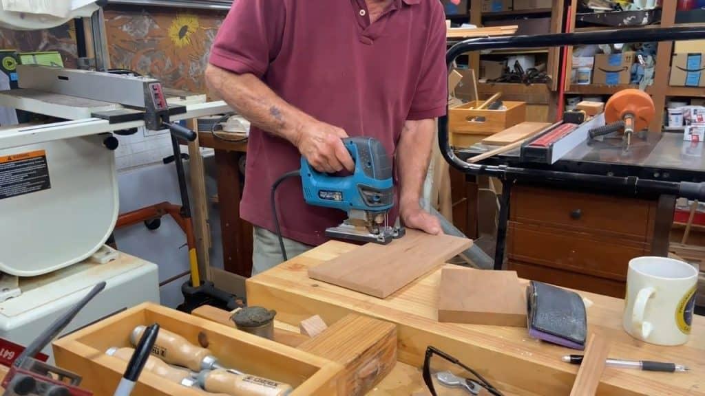 Man cutting plywood using a jigsaw