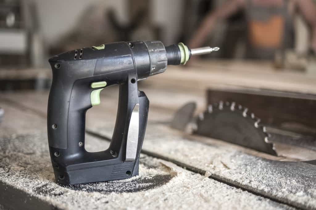 Drill on top of an old table saw that needs a clean up