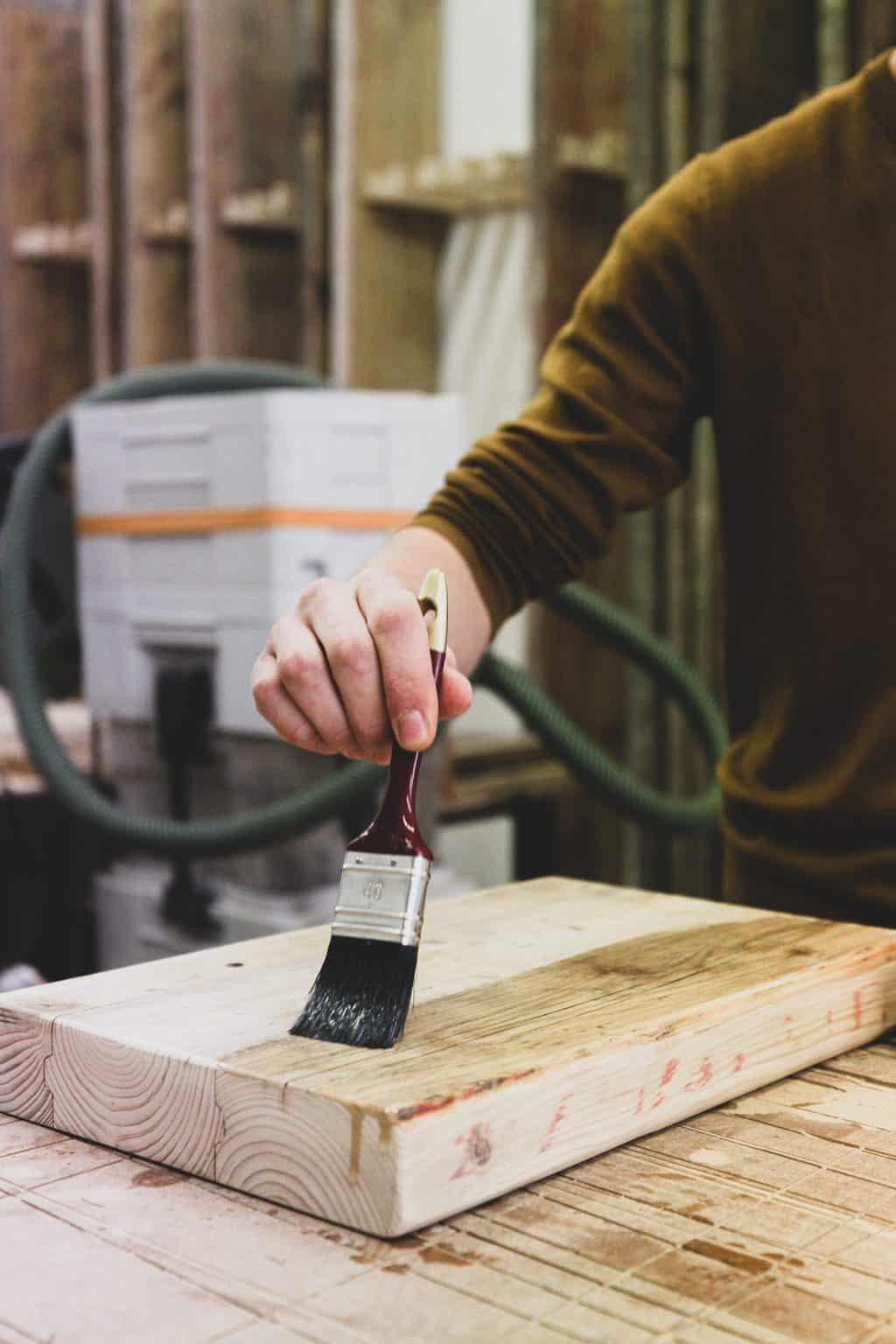 Man applying finish on a block of wood