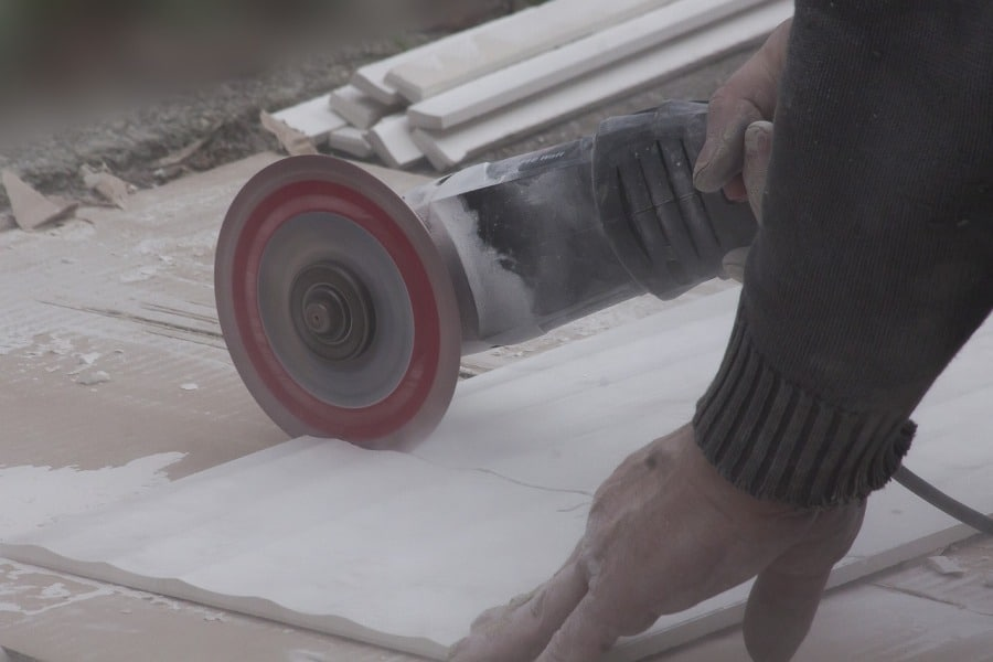 Person using an angle grinder to cut through a material