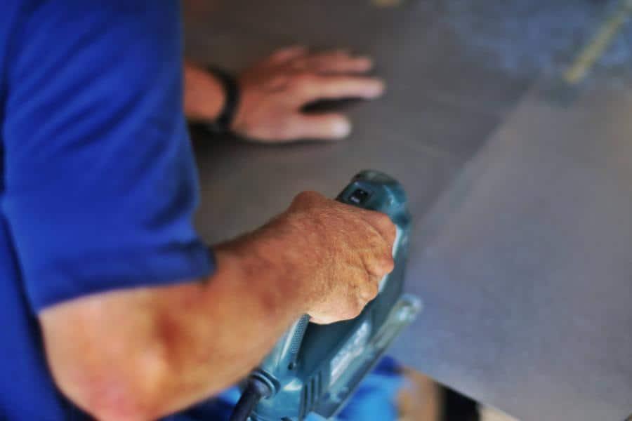 Person using a jigsaw to cut plexiglass