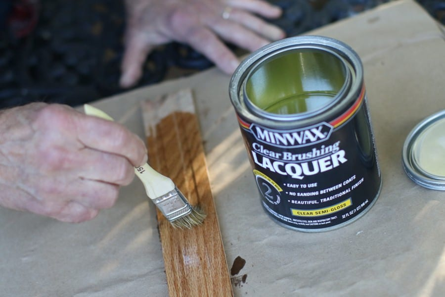 Man applying lacquer on a strip of wood