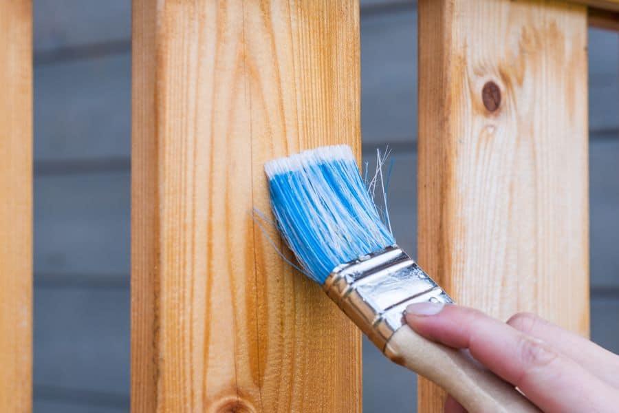 Person brushing varnish on wood