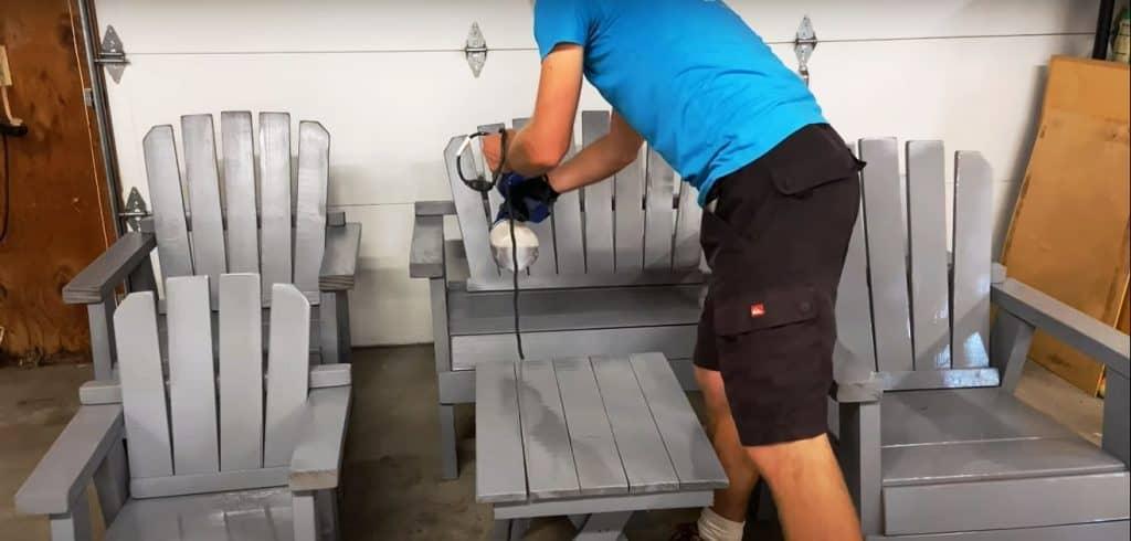 Man using a paint sprayer to apply Spar varnish on furniture
