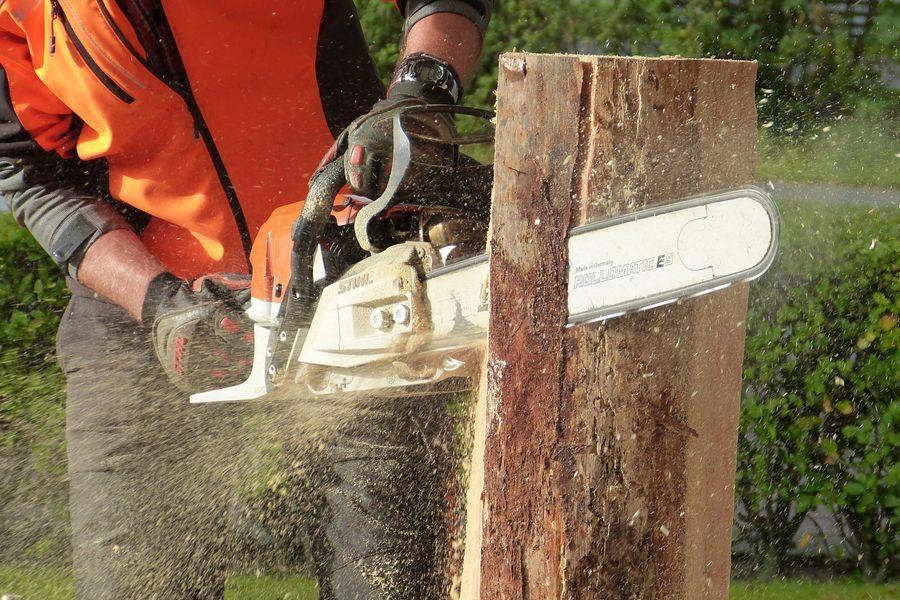Man using a chainsaw to cut wood log