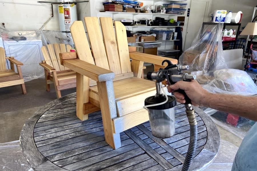 Man using an HVLP paint sprayer to paint a chair